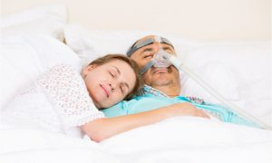 a wife with her husband using a CPAP device